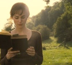Young woman reading book, standing, in nature