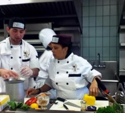Photograph, by Claire Stewart, is of chefs Adrienne Jones and David Caban competing in the Kitchen Feud at the New York City College of Technology on April 25, 2013.