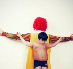 Ronald McDonald and Boy, arms spread, Christ-like
