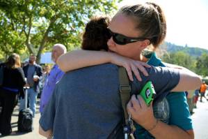 A woman is comforted as friends and family wait for students at the local fairgrounds after a shooting at Umpqua Community College in Roseburg, Ore., on Thursday, Oct. 1, 2015. (AP Photo/Ryan Kang)