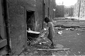 "Nick Hedges, ""Make life worth living,"" photographs for Shelter; mother takes her baby inside her condemned tenement block, Gorbals, 1970"