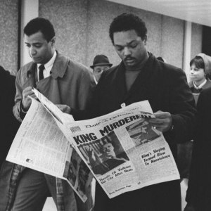 Jesse Jackson reading newspaper telling of Martin Luther King Jr.'s assassintation