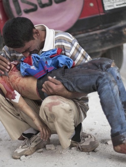 A Syrian man holds lifeless body of his son, killed by Syrian Army, Aleppo, Syria, October 3, 2013, photo by Manu Brabo - AP